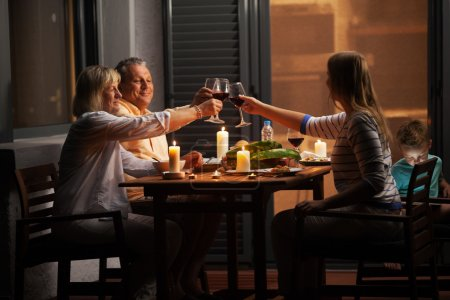 Photo pour Dîner de famille en plein air dans l'arrière-cour en soirée tranquille. Jeune femme et parents aînés griller avec le vin tandis que l'enfant jouant à des jeux - image libre de droit