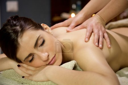 Beautiful woman relaxing in spa getting massage in vacation
