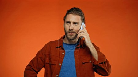 Photo for Confused young man talking on mobile phone on orange - Royalty Free Image