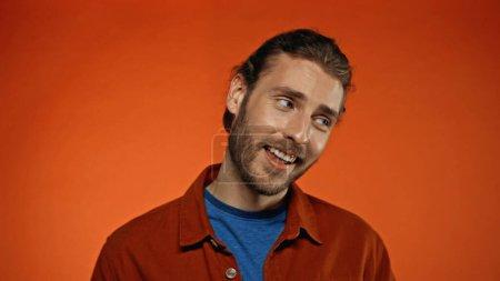 homme joyeux et barbu souriant tout en regardant loin sur l'orange