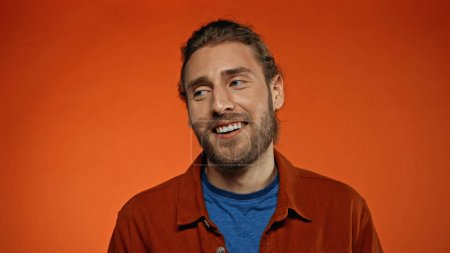pleased and bearded man smiling while looking away on orange