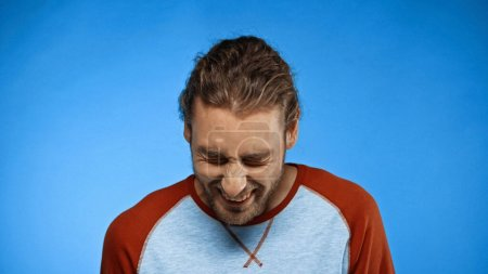 Photo for Bearded young man with closed eyes laughing on blue - Royalty Free Image