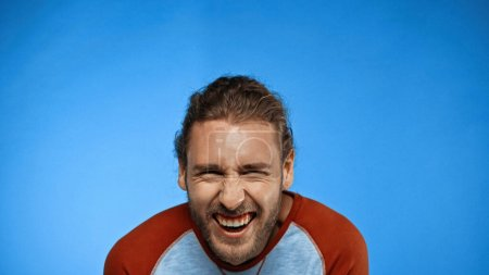 bearded young man looking at camera and laughing on blue