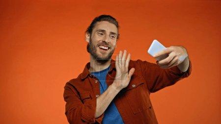 Photo pour Barbu jeune homme agitant la main tout en ayant appel vidéo sur orange - image libre de droit