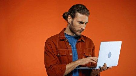 bearded young man using laptop on orange