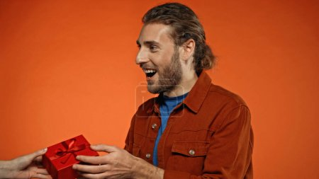 glücklicher junger Mann erhält verpacktes Geschenk in Orange