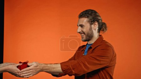 happy man giving wrapped present to woman on orange