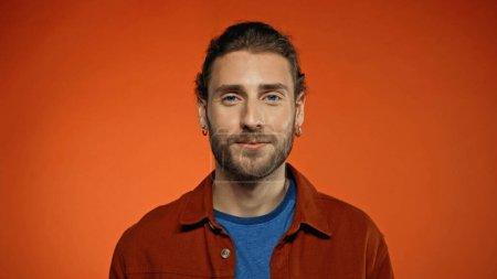 Photo pour Heureux barbu homme regardant caméra sur fond orange - image libre de droit