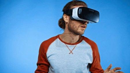 joven sorprendido en auriculares de realidad virtual en azul