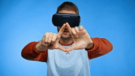 bearded young man in virtual reality headset gesturing on blue