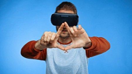 Foto de Hombre joven barbudo en auriculares de realidad virtual gestos en azul - Imagen libre de derechos