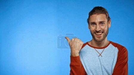 Photo pour Homme joyeux pointant avec le pouce sur le bleu - image libre de droit