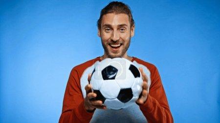 Photo pour Fan de football positif tenant ballon de football sur bleu - image libre de droit