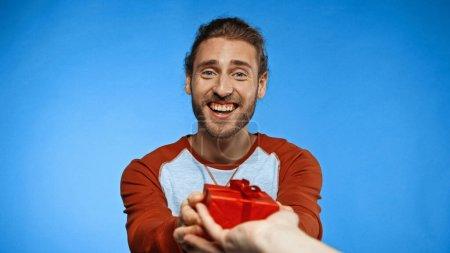 fröhlicher Mann beschenkt Frau auf blauem Grund