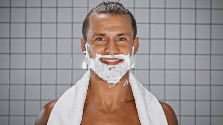 positive man with shaving foam on face looking at camera in bathroom