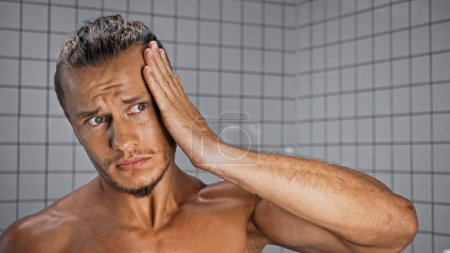 Photo pour Torse nu jeune homme fixant les cheveux dans la salle de bain - image libre de droit