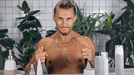 Photo pour Homme torse nu pointant avec les doigts tout en regardant la caméra près de plantes vertes sur fond flou dans la salle de bain - image libre de droit