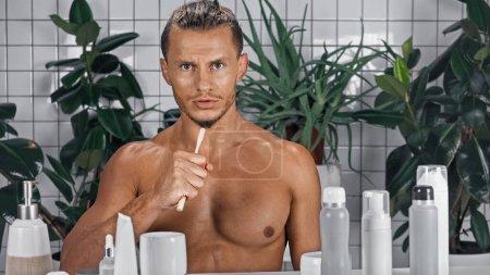 Photo pour Homme torse nu tenant une brosse à dents près de plantes vertes sur fond flou dans la salle de bain - image libre de droit