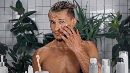 Photo pour Homme torse nu touchant visage près de plantes vertes sur fond flou dans la salle de bain - image libre de droit