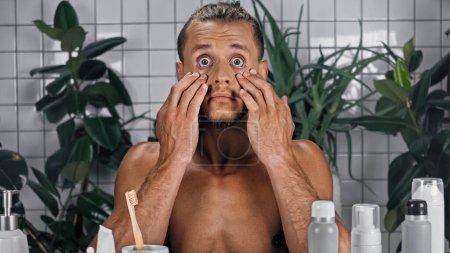 Photo pour Homme torse nu choqué toucher le visage près de plantes vertes sur fond flou dans la salle de bain - image libre de droit