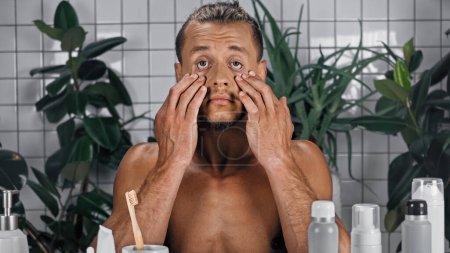 Photo pour Jeune homme torse nu touchant le visage près de plantes vertes sur fond flou dans la salle de bain - image libre de droit
