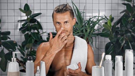 Photo pour Homme barbu appliquer crème visage dans la salle de bain avec des plantes sur fond flou - image libre de droit