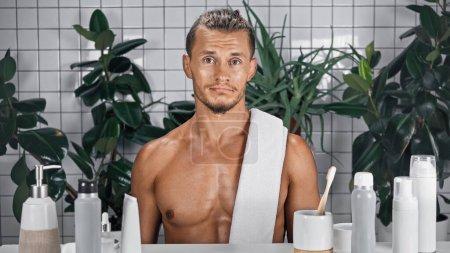 Photo pour Homme barbu avec serviette sur corps torse nu dans la salle de bain près de plantes sur fond flou - image libre de droit