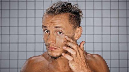 bearded man touching skin near eye looking at camera in bathroom