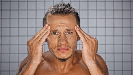 Photo pour Homme barbu regardant caméra et rides touchantes dans la salle de bain - image libre de droit