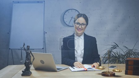 Photo for Smiling insurance agent looking at camera near devices, statuette of justice and scales in office - Royalty Free Image