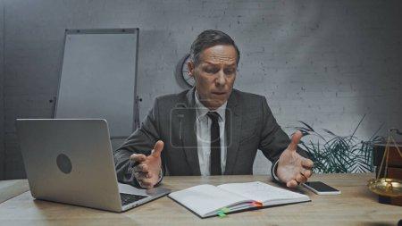 Photo pour Agent d'assurance inquiet regardant le carnet près des appareils et des balances au premier plan flou - image libre de droit
