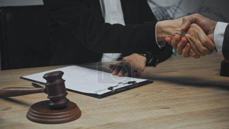 Photo pour Vue recadrée des agents d'assurance serrant la main près des documents et du marteau - image libre de droit