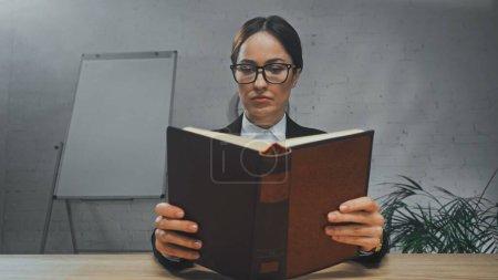 Photo pour Livre de lecture de l'agent d'assurance à table au bureau - image libre de droit