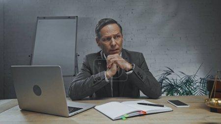 Photo pour Agent d'assurance réfléchi regardant loin près des appareils, carnet et balances sur la table de travail - image libre de droit