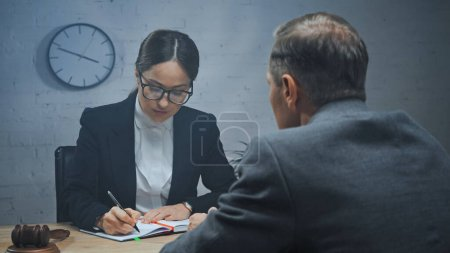 Insurance agent writing on notebook near gavel and colleague on blurred foreground