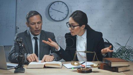 Agente de seguros que muestra gesto de encogimiento de hombros cerca de colega leyendo libro, portátil y escalas en la oficina