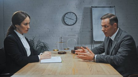 Insurance agent talking to colleague with notebook near books and scales on table