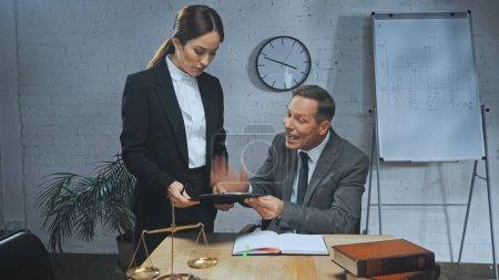 Photo pour Agent d'assurance agressif tenant presse-papiers près d'un collègue, ordinateur portable et balances au bureau - image libre de droit