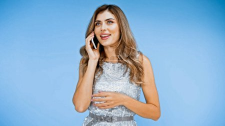 cheerful woman with wavy hair talking on smartphone on blue