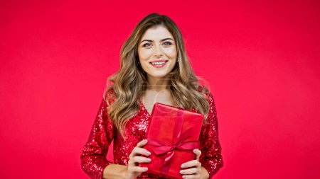 happy woman with wavy hair holding present isolated on red