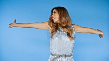 cheerful woman with outstretched hands looking away isolated on blue