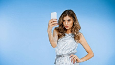 Photo for Woman pouting lips while taking selfie and standing with hand on hip on blue - Royalty Free Image