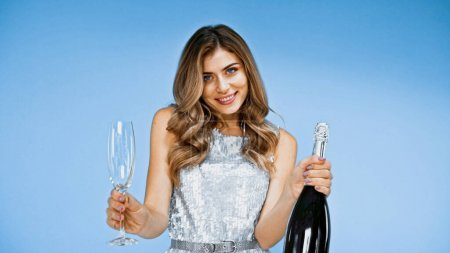 happy woman holding glass with champagne and bottle on blue