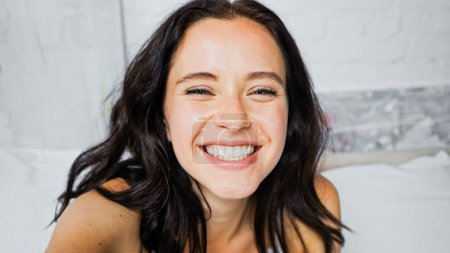 portrait of excited brunette woman smiling at camera in bedroom