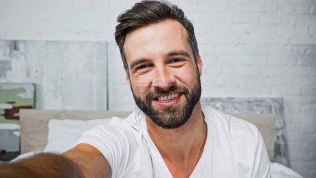 Photo for Happy bearded man smiling at camera in bedroom - Royalty Free Image