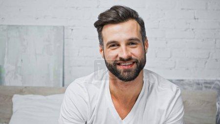 Photo pour Jeune homme barbu souriant tout en regardant la caméra dans la chambre - image libre de droit