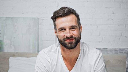 joyful bearded man smiling at camera while sitting in bedroom