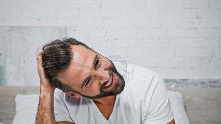 happy bearded man touching head in bedroom in morning