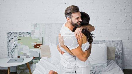 Photo pour Heureux barbu homme étreignant petite amie dans chambre - image libre de droit