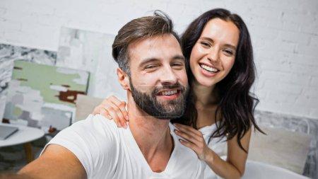 Foto de Hombre barbudo feliz y mujer morena sonriendo a la cámara en el dormitorio - Imagen libre de derechos